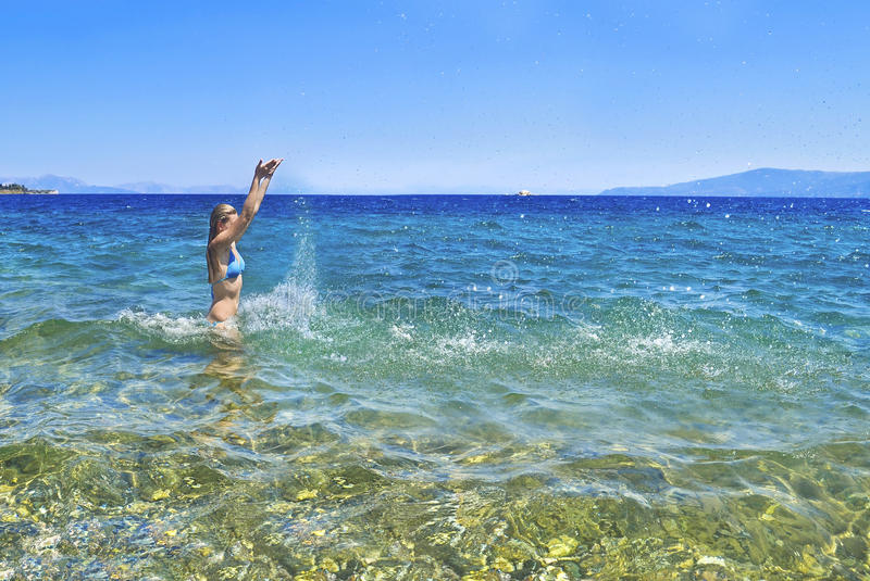 Greek girl playing with the waves at Euboea Greece stock photo