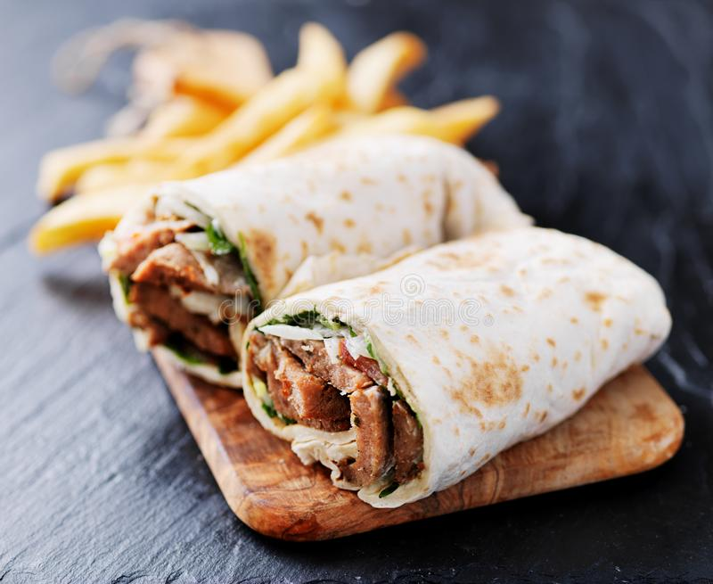 Greek gyro wrap cut in half and served with fries stock photography