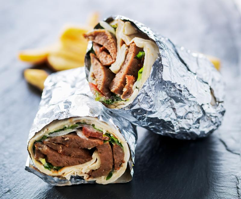 Greek gyro wrapped in foil cut in half and served with fries stock photos
