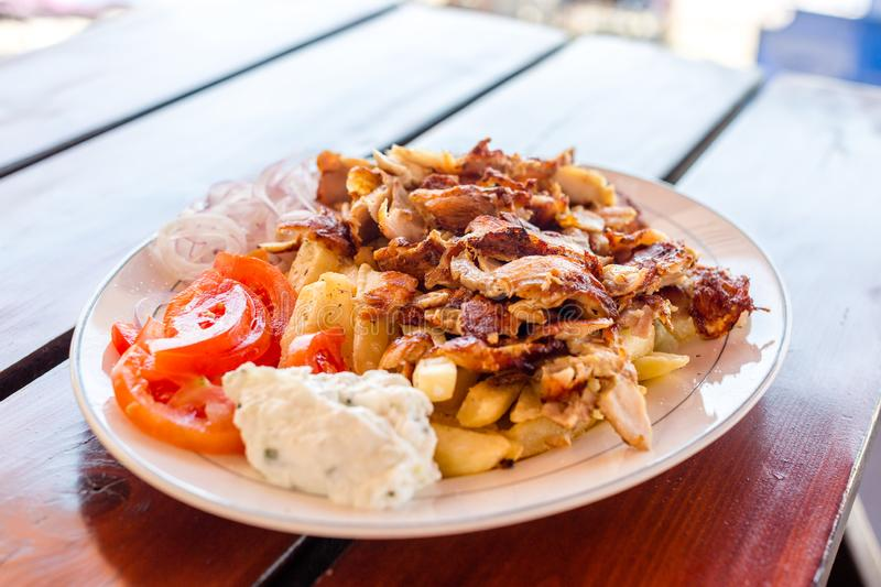 Greek gyros with french fries, vegetables and tzatziki sauce on white plate stock photos