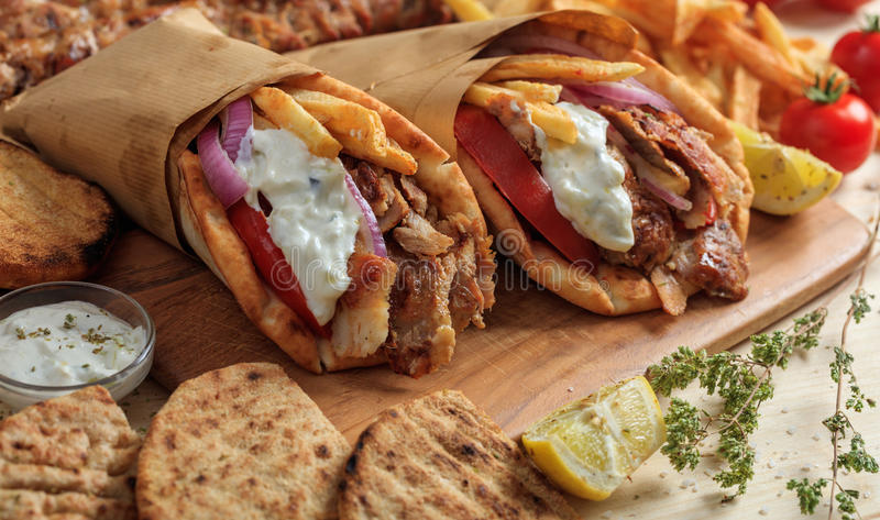 Greek gyros wrapped in pita breads on a wooden table stock image