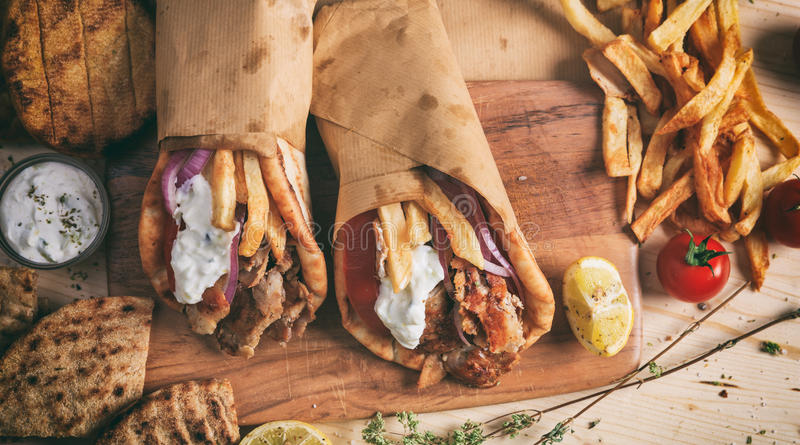 Greek gyros wrapped in pita breads on a wooden table - top view royalty free stock image