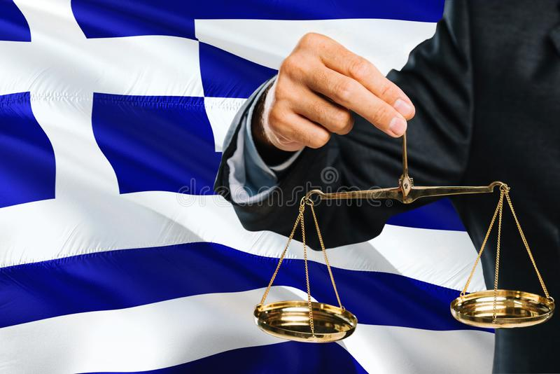 Greek Judge is holding golden scales of justice with Greece waving flag background. Equality theme and legal concept stock images