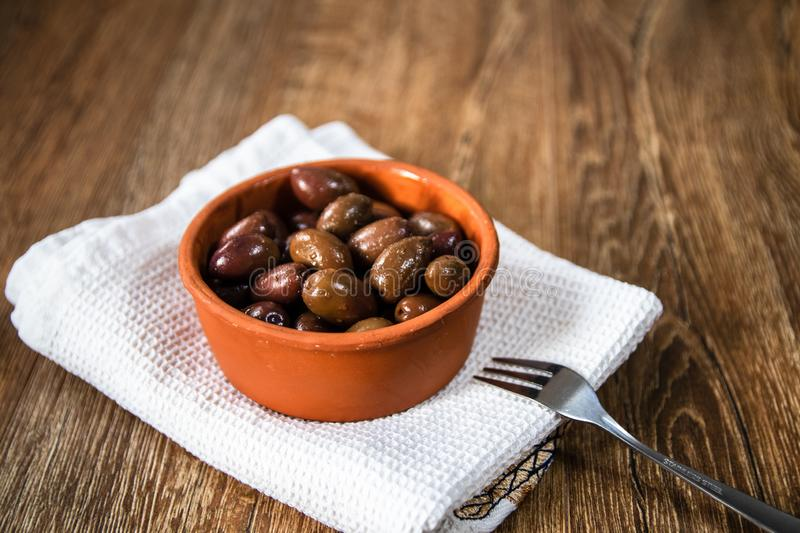 Greek Kalamata black red olives in a clay bowl. On wooden table royalty free stock photography
