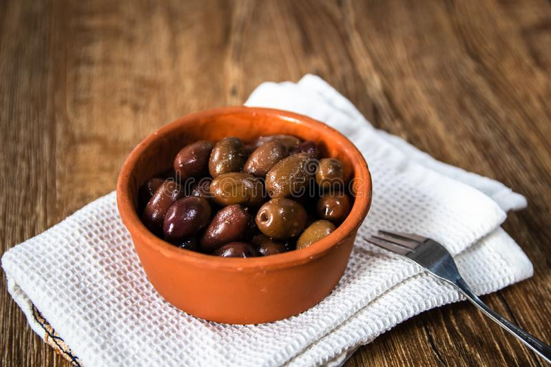Greek Kalamata black red olives in a clay bowl. On wooden table royalty free stock image