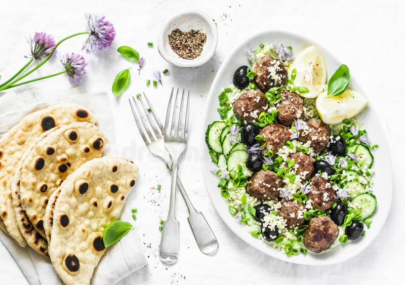 Greek lamb meatballs with avocado greek yogurt sauce, couscous and whole grain flatbread on a light background, top view. Mediterr. Anean style food stock photos