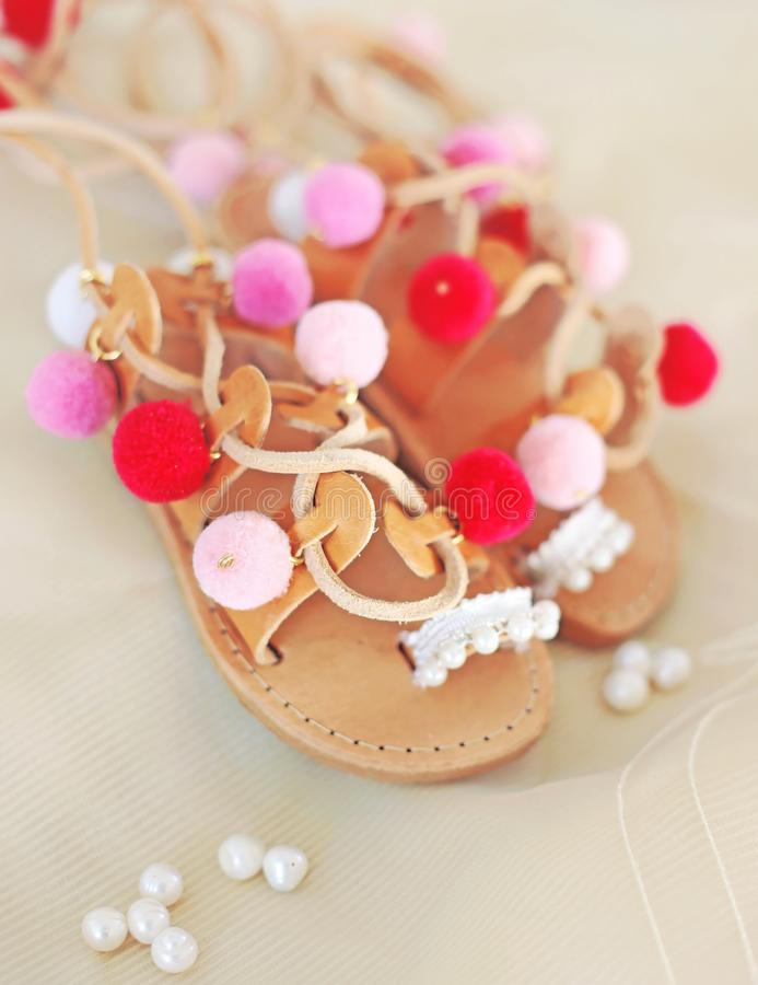 Greek leather sandals for girls with colorful pom pom - gladiator sandals royalty free stock photography
