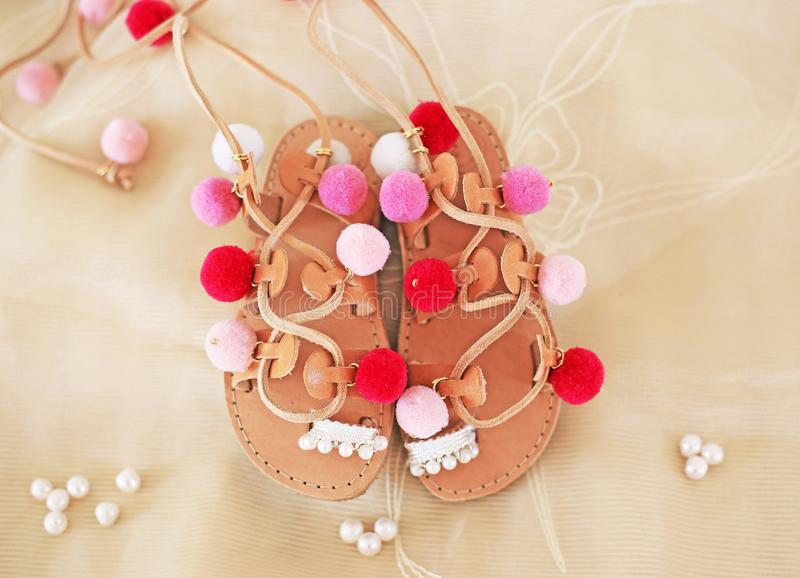 Greek leather sandals for girls with colorful pom pom - gladiator sandals royalty free stock images