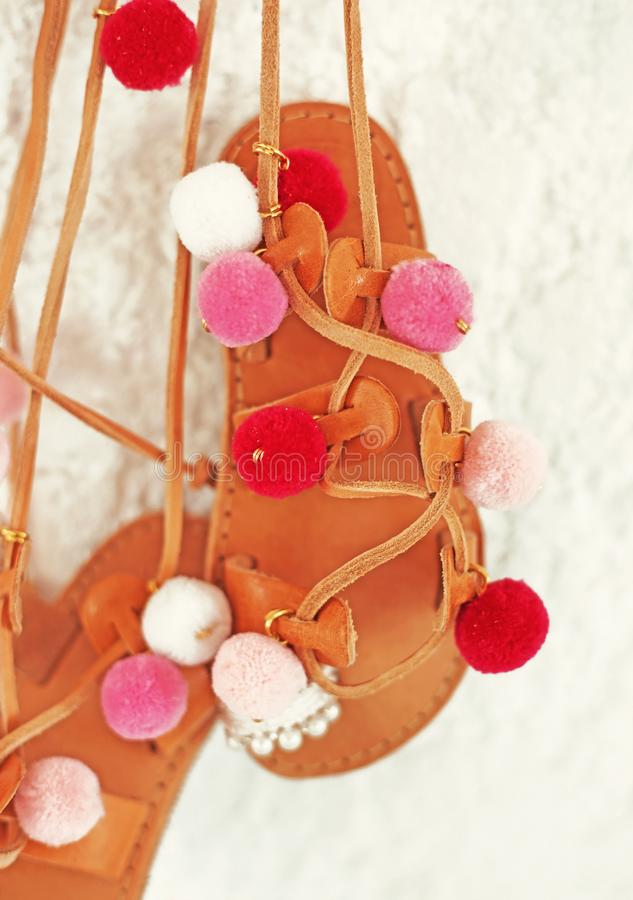 Greek leather sandals for girls with colorful pom pom - gladiator sandals stock photography