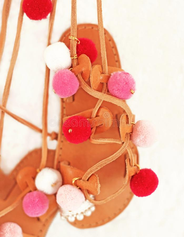 Greek leather sandals for girls with colorful pom pom - gladiator sandals stock photo