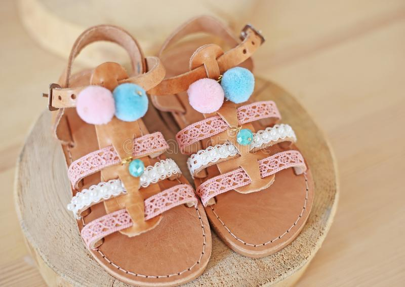 Greek leather sandals with pom pom for girls - kids shoes advertisement stock photos