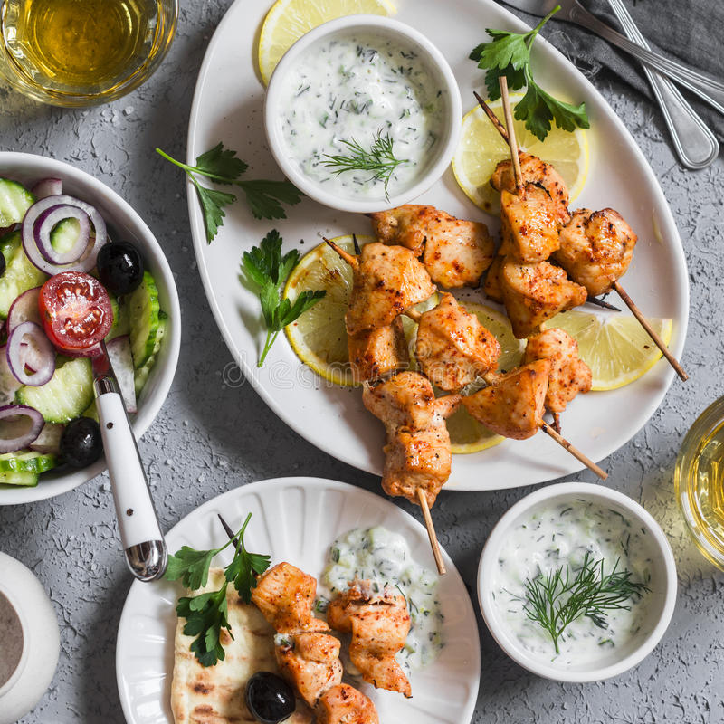 Greek lunch - chicken kebabs, greek salad, tzatziki, flatbreads and white wine. On a light background royalty free stock photo
