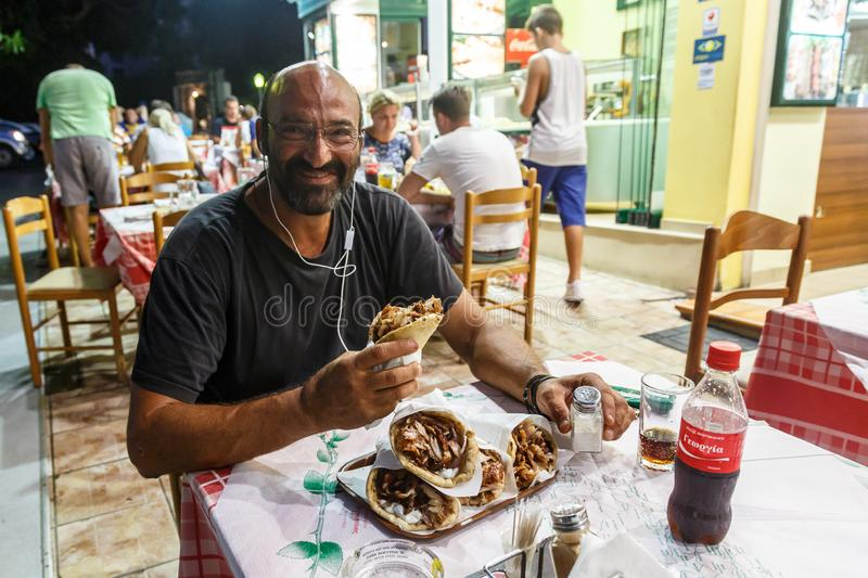 Greek man eating traditional local fast food gyros in a street taverna on Rhodes Island, Dodecanese, Greece royalty free stock image