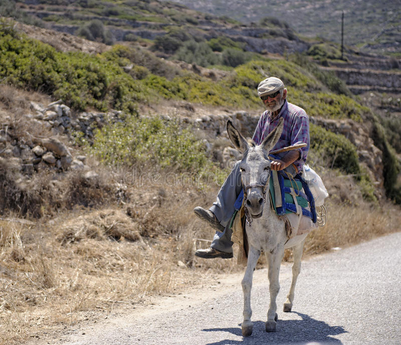 Greek man riding donkey royalty free stock photo