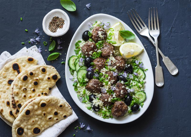 Greek meatballs with avocado greek yogurt sauce, couscous and whole grain flatbread on a dark background, top view. Mediterranean. Style food royalty free stock image