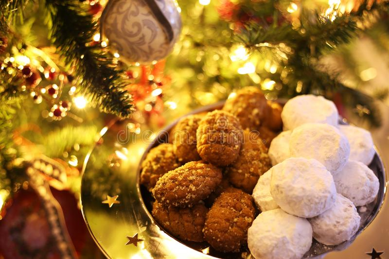 Greek melomakarona and kourabies in front of the Christmas tree - traditional Christmas cookies with honey and nuts and sugar buns stock photo