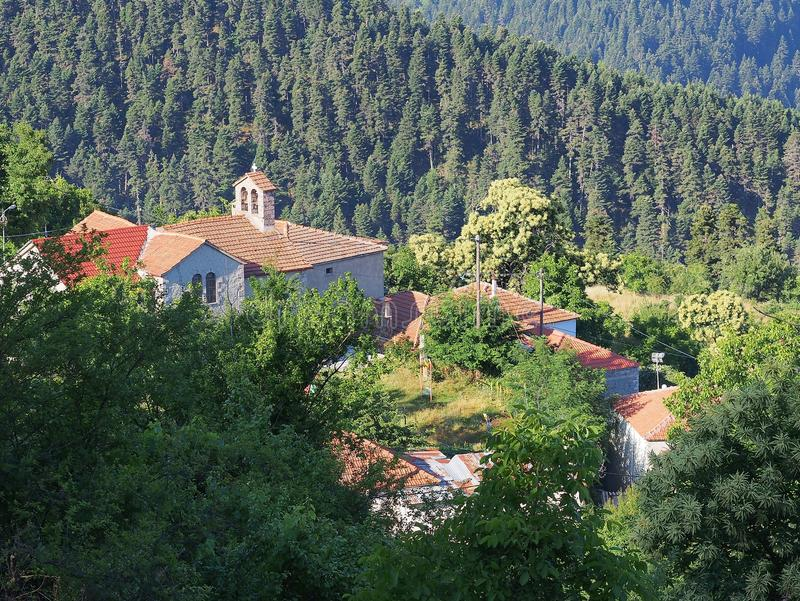 Greek Mountain Village. Orthodox church and houses in remote Greek mountain village set amongst pine forests royalty free stock images