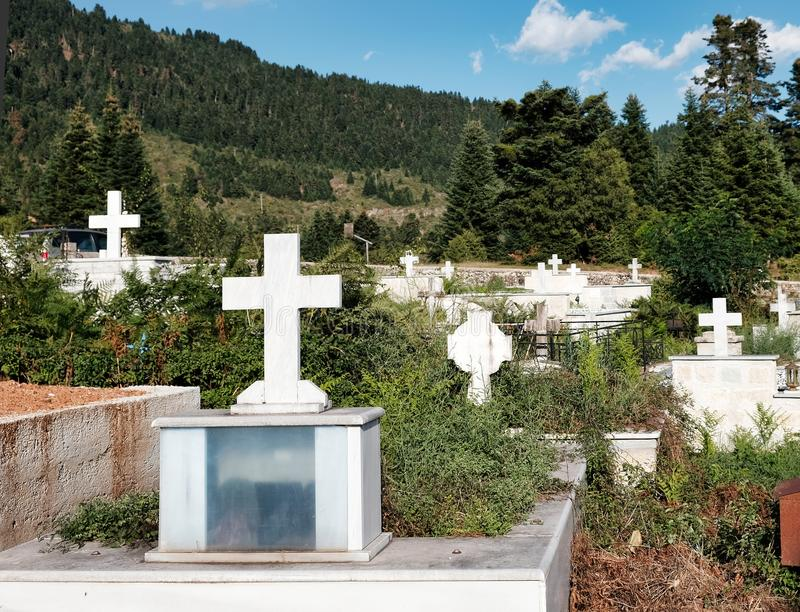 White Marble Crosses in Greek Mountain Cemetery. A Greek Orthodox cemetery on a pine forest covered mountain, with white marble crosses on graves amongst long stock photos