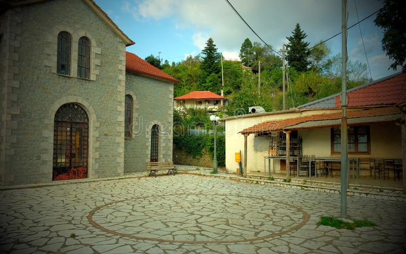 Nostalgic Vignette, Deserted Greek Mountain Village, Greece. Greek Orthodox church and cafe in the main square, or plaeia, of a small Greek mountain village royalty free stock images