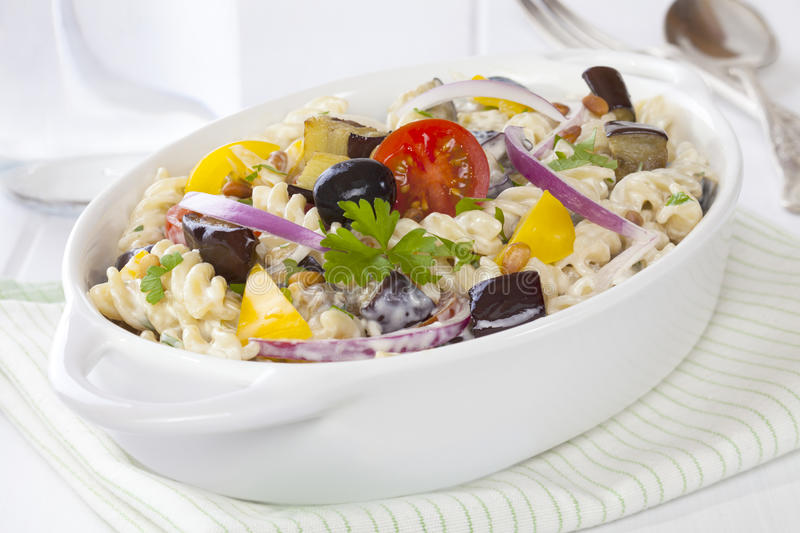 Greek Pasta Salad. Greek style pasta salad with eggplant, black olives, tomatoes, red onion and yellow capsicum in a creamy dressing royalty free stock photography