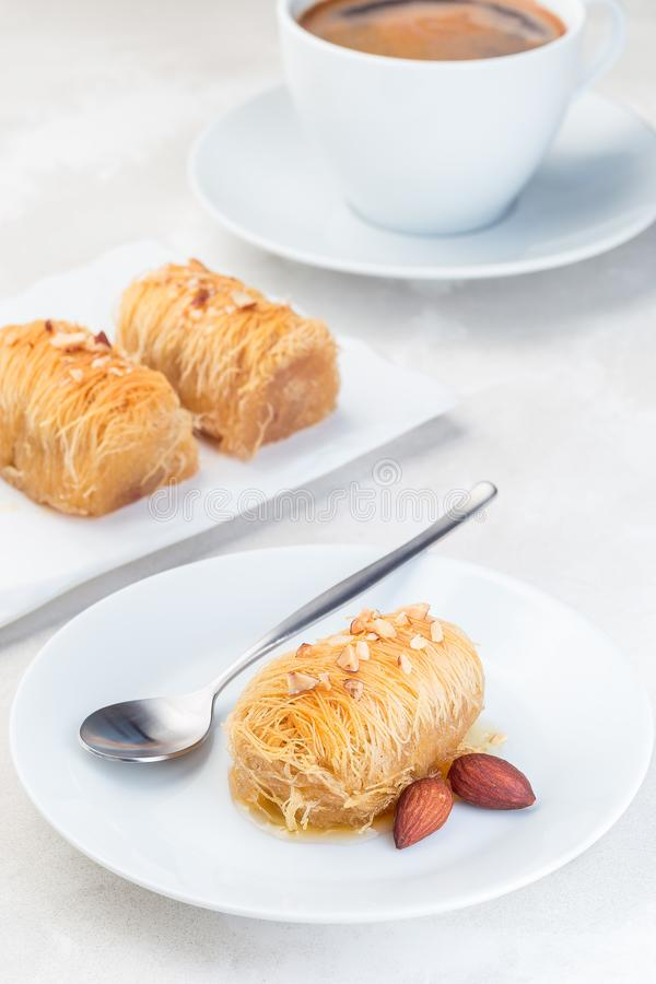 Greek pastry Kataifi with shredded filo dough stuffed with almond nuts, in honey syrup, on white plate, served with cup of coffee stock photography
