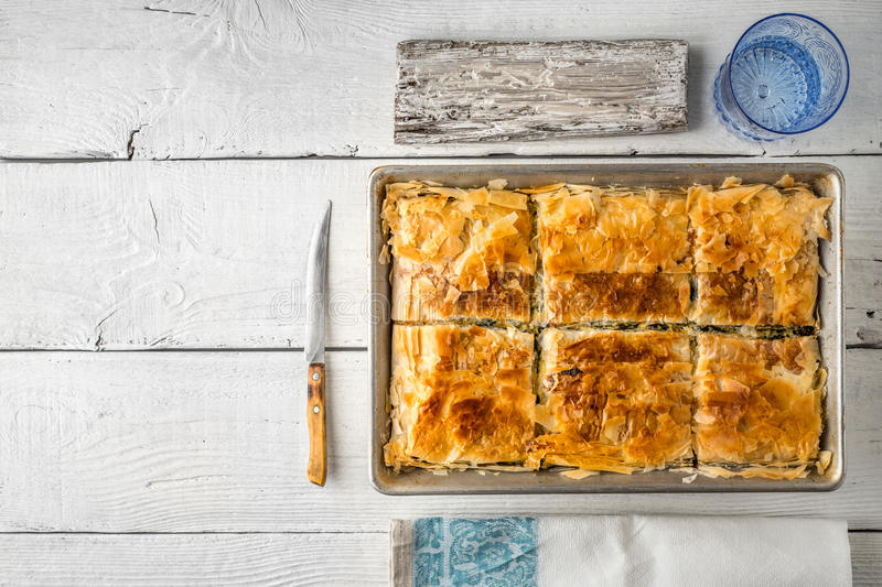 Greek pie spanakopita in the metal pan with table ware horizontal. Greek pie spanakopita in the metal pan on the white wooden table with table ware top view royalty free stock images