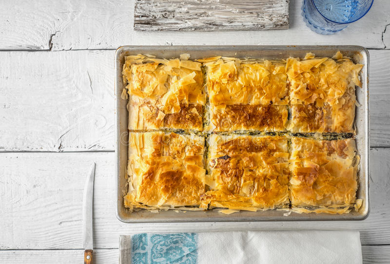 Greek pie spanakopita in the metal pan with table ware top view. Greek pie spanakopita in the metal pan on the white wooden table with table ware top view royalty free stock photos