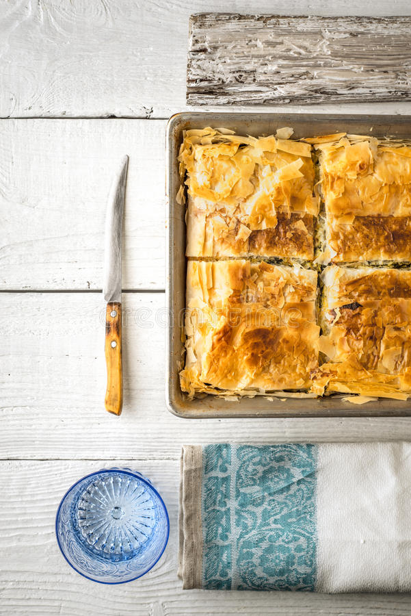Greek pie spanakopita in the metal pan with table ware vertical. Greek pie spanakopita in the metal pan on the white wooden table with table ware top view royalty free stock photo