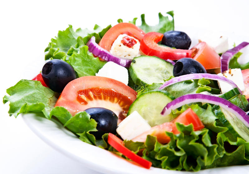 Greek salad. A plate with green salad leafes, cucumber, feta,red onion and olives
