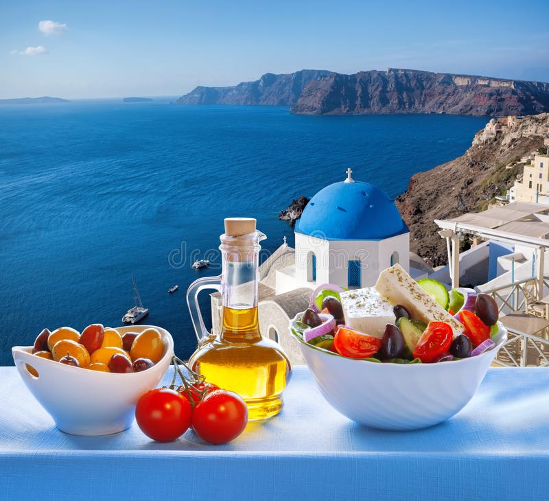 Greek salad against famous church in Oia village, Santorini island in Greece stock photos