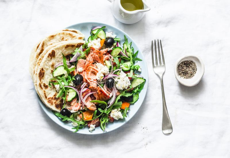 Greek salad with baked salmon on a light background, top view. Healthy mediterranean diet food. Greek salad with baked salmon on a light background, top. Healthy royalty free stock photo