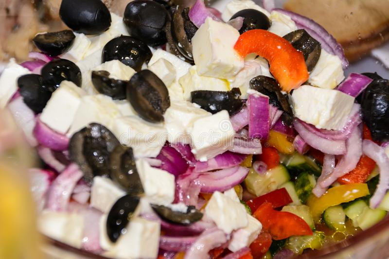 Greek salad, in close-up. Tomatoes, black olives, red onions, cucumber, rosemary, sweet pepper, feta cheese and olive oil. Healthy food royalty free stock photography