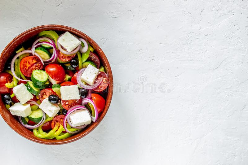 Greek salad on a concrete background. Tomatoes, peppers, olives, cheese, onions. Healthy eating. Diet. Vegetarian food. Greek salad on a concrete background royalty free stock image
