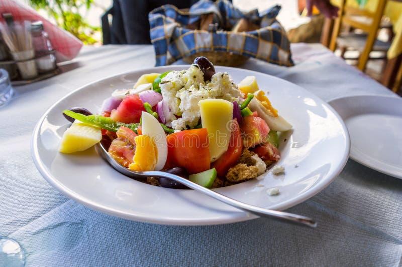 Greek salad on Crete island with egges and potato. Crete island, Greece stock photography
