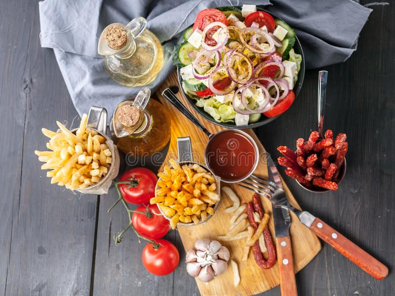 Greek salad with feta cheese, french fries, smoked sausages, tomatoes and garlic. Tasty food on a rustic background. Top view stock photos