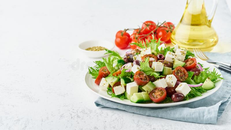Greek Salad with feta and tomatoes, dieting food on white background copy space closeup long banner. Greek Salad with feta cheese, olives, cherry tomato royalty free stock image