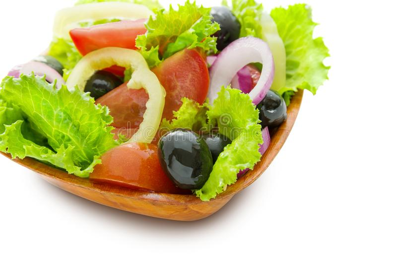 Greek salad of fresh bright vegetables in a wooden plate isolated on white background stock image