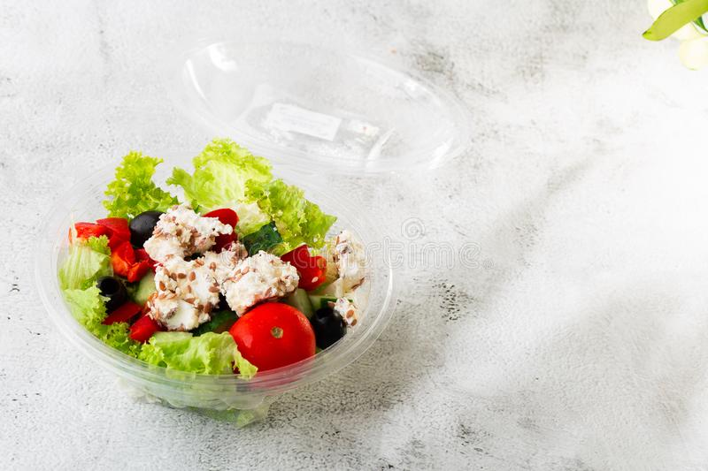 Greek salad of fresh cucumber, tomato, sweet pepper, lettuce, red onion, feta cheese and olives with olive oil isolated on white stock photo