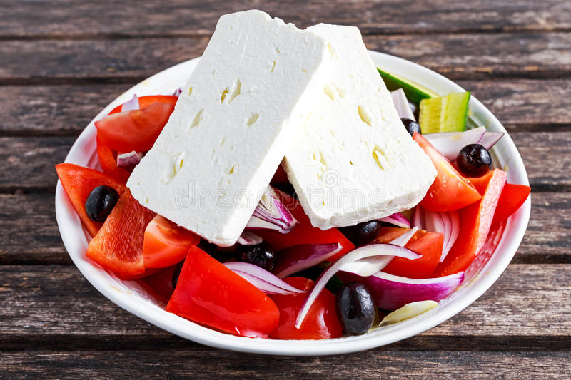 Greek salad with fresh sweet pepper, red onion, cucumber, black olives and feta chees drizzled extra virgin olive oil stock photos