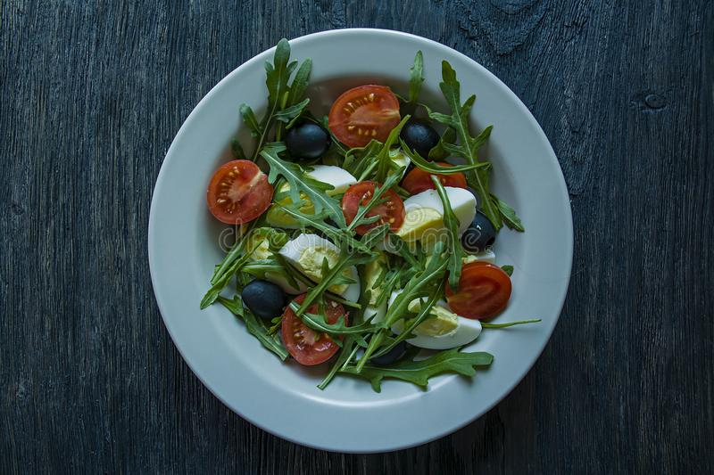 Greek salad with fresh tomatoes, arugula, eggs, olives with olive oil on a dark wood background. Healthy food. Veggie dish royalty free stock photo