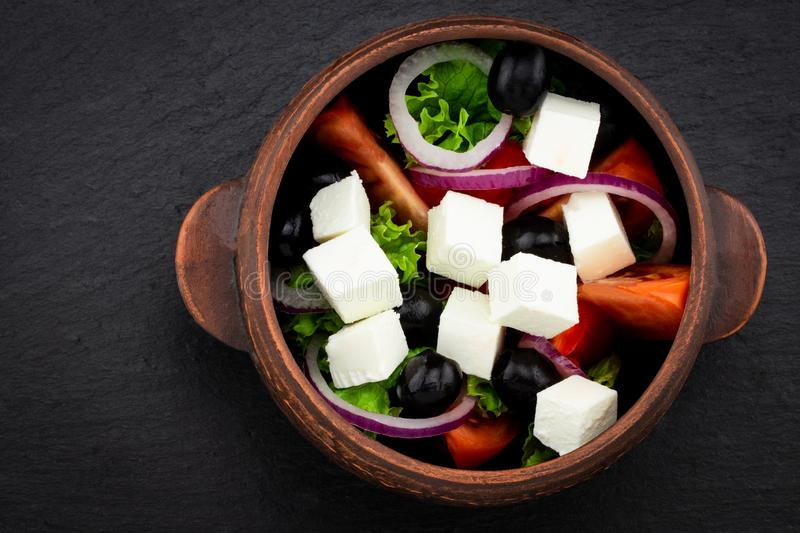 Greek salad with fresh vegetables, feta cheese and black olives. On a dark background. Top view stock photo