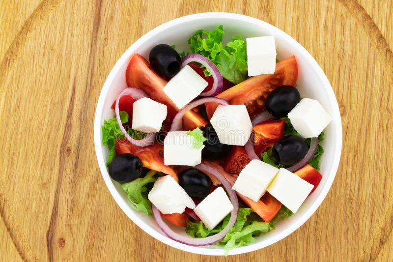 Greek salad with fresh vegetables, feta cheese and black olives. On a wooden background. Top view stock image