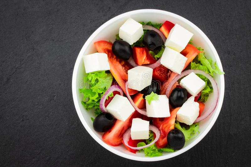 Greek salad with fresh vegetables, feta cheese and black olives. On a dark background. Top view royalty free stock photos