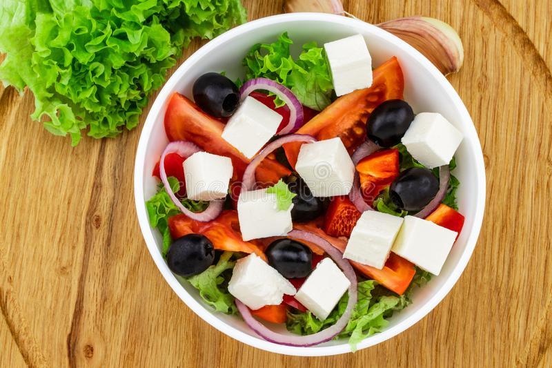 Greek salad with fresh vegetables, feta cheese and black olives on a wooden background. Top view.  royalty free stock photos