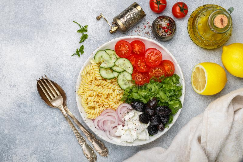 Greek salad with fusilli paste, lettuce, tomatoes, cucumber, feta cheese, red onions and black olives. Dressed with olive oil. A delicious Mediterranean royalty free stock photo
