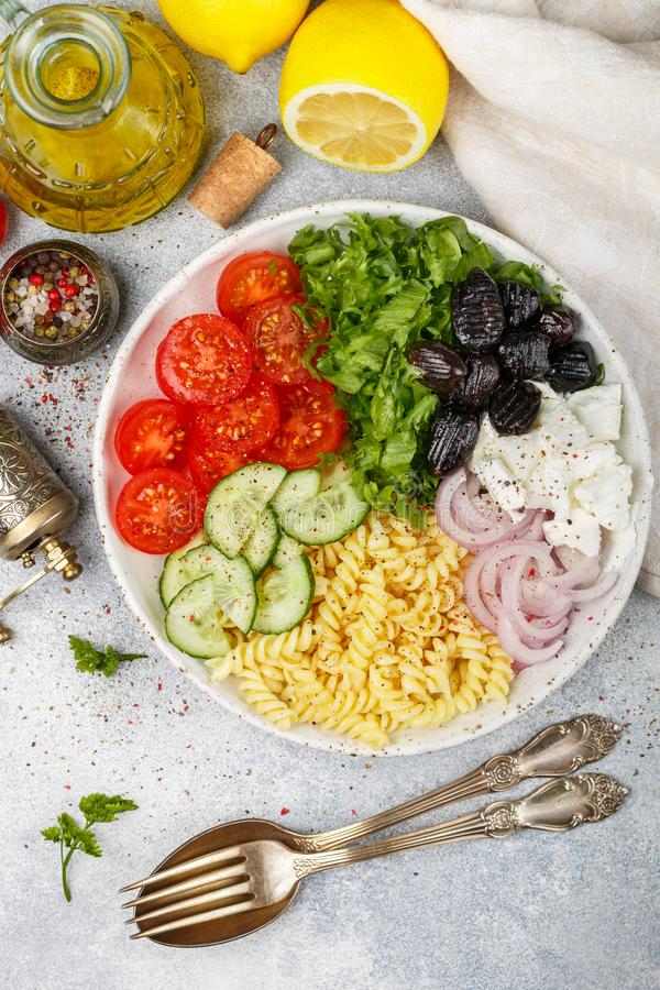 Greek salad with fusilli paste, lettuce, tomatoes, cucumber, feta cheese, red onions and black olives. Dressed with olive oil. A delicious Mediterranean stock photography