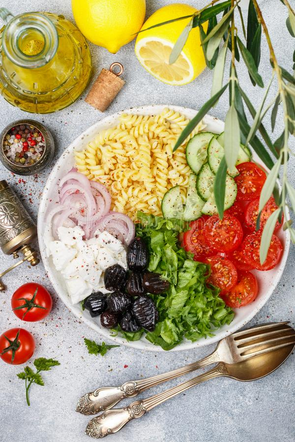 Greek salad with fusilli paste, lettuce, tomatoes, cucumber, feta cheese, red onions and black olives. Dressed with olive oil. A delicious Mediterranean royalty free stock images