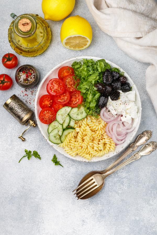 Greek salad with fusilli paste, lettuce, tomatoes, cucumber, feta cheese, red onions and black olives. Dressed with olive oil. A delicious Mediterranean stock image