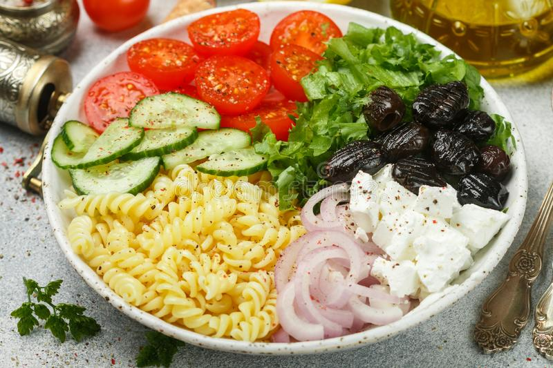 Greek salad with fusilli paste, lettuce, tomatoes, cucumber, feta cheese, red onions and black olives. Dressed with olive oil. A delicious Mediterranean royalty free stock image