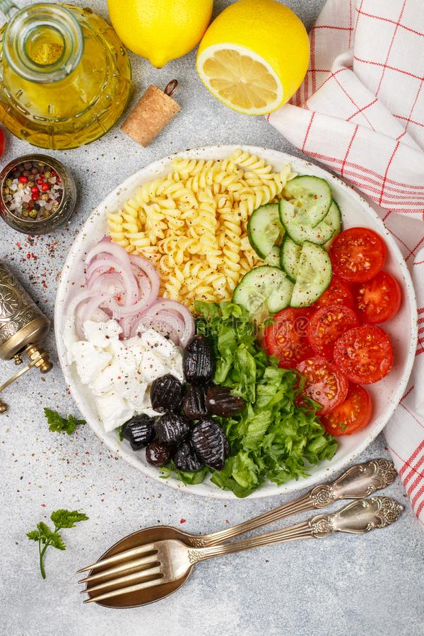 Greek salad with fusilli paste, lettuce, tomatoes, cucumber, feta cheese, red onions and black olives. Dressed with olive oil. A delicious Mediterranean royalty free stock photos